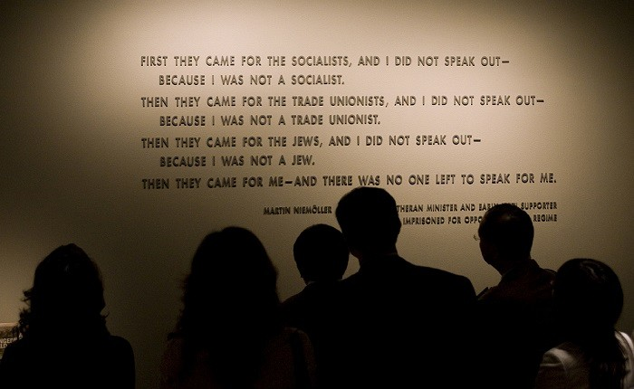 """<p>Visitors stand in front of the quotation from <a href=""""/narrative/10764"""">Martin Niemöller</a> that is on display in the Permanent Exhibition of the United States Holocaust Memorial Museum. Niemöller was a Lutheran minister and early Nazi supporter who was later imprisoned for opposing Hitler's regime.</p>"""