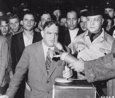 Former mayor of New York Fiorello H. La Guardia, on a tour of United Nations Relief and Rehabilitation Administration (UNRRA) camps in Europe, speaks to survivors.