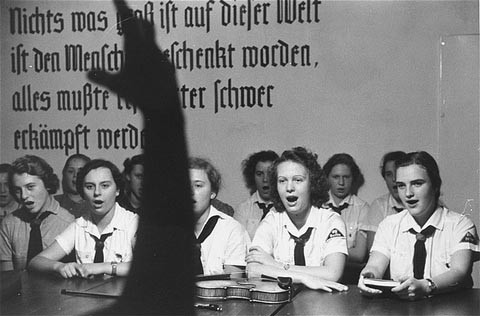 German girls, members of a Hitler youth organization, follow their leader in song.