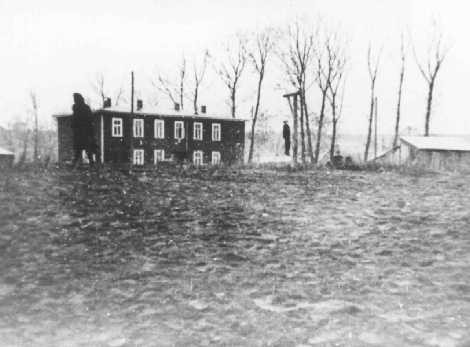 In the Kovno ghetto, the body of a Jewish man executed on German orders hangs from gallows erected near the Jewish council building.