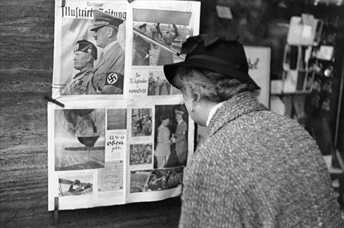 <p>In Berlin, a German woman reads a copy of the <em>Berliner Illustrierte</em> newspaper, featuring photographs of Mussolini's official visit to Berlin in September 1937.</p>
