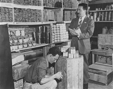 "<p>Morris Laub (right), <a href=""/narrative/5002"">American Jewish Joint Distribution Committee</a> director for <a href=""/narrative/26091"">Cyprus</a>, reviews supplies sent for the 12,000 Jews still interned on the island. Cyprus, December 9, 1948.</p>"