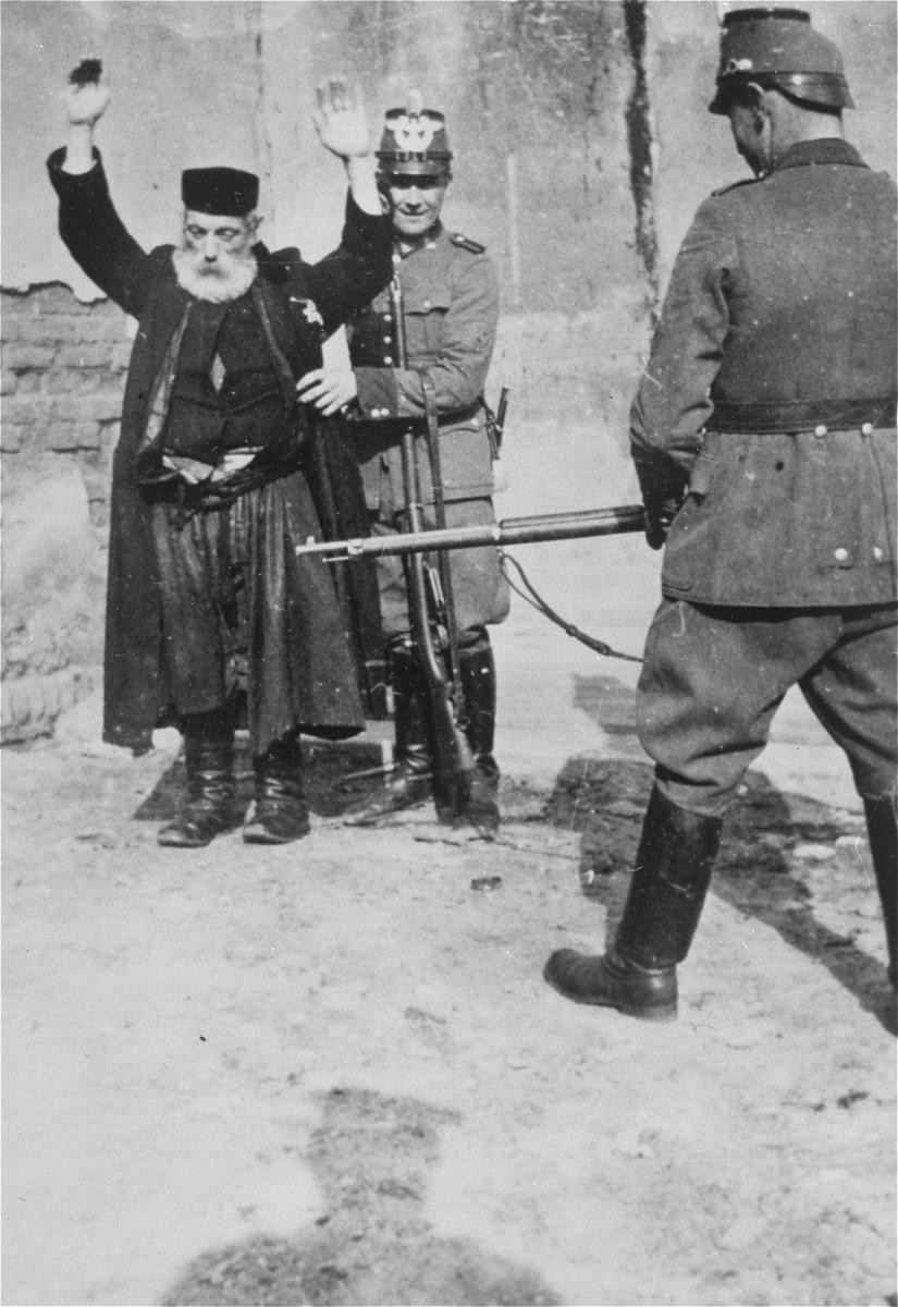 "<p>German policemen search an elderly, religious Jew at gunpoint in German-occupied <a href=""/narrative/2103"">Poland</a>, circa 1941.</p>"