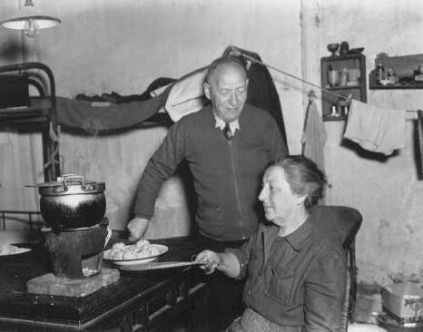 "<p>A Jewish refugee family prepares food with rations provided by the <a href=""/narrative/7232"">United Nations Relief and Rehabilitation Administration</a> (UNRRA). Shanghai, China, 1946.</p>"