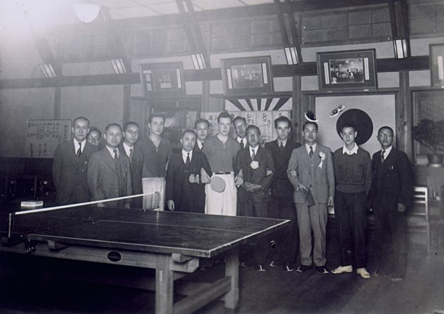 <p>Jewish refugees pose for a picture with Japanese men. Samuel Schiff  (center, holding the paddle) was the table tennis champion of Poland. He played matches during his stay in Japan. Kobe, Japan, May 29, 1941.</p>