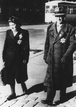 <p>یک زوج یهودی که آرم مشخص کننده یهودیان را بر لباس دارند. استفاده از این آرم اجباری بود. آلمان، 27 سپتامبر 1941.</p>