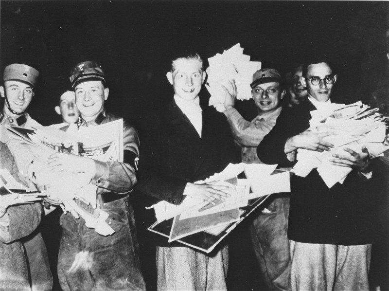 "Students and members of the SA with armfuls of literature deemed ""un-German"" during the book burning in Berlin. [LCID: 69031]"