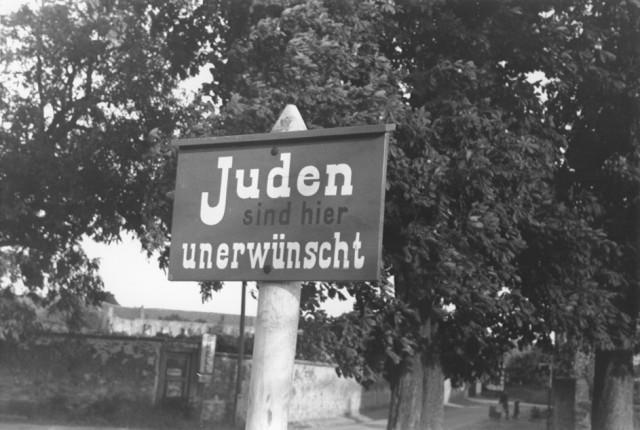 """<p>Sebuah tanda anti-Yahudi ditempel di jalan di Bavaria yang berbunyi """"Orang Yahudi yang tidak diinginkan di sini."""" Jerman, 1937.</p>"""