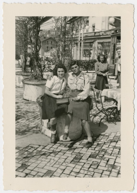 Two women who came to Switzerland on the Kasztner tranport pose together at an outdoor cafe.