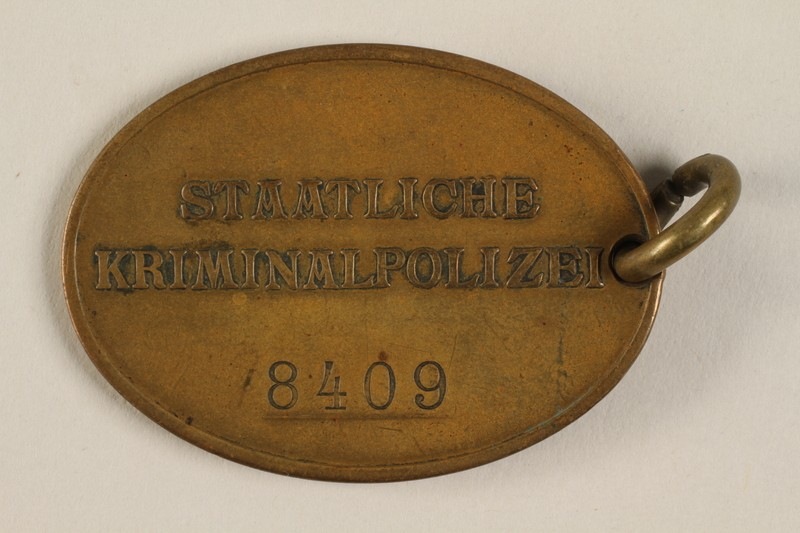 "<p>Reverse of the official identification tag (warrant badge) for the <em>Kriminalpolizei</em> or <a href=""/narrative/63226"">Kripo</a>, the detective police force of <a href=""/narrative/2529"">Nazi Germany</a>. It reads <em>Staatliche Kriminalpolizei</em> (State Criminal Police) and identifies the officer's number as 8409.</p>"