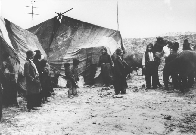"""<p>Scene from a Romani (Gypsy) camp:<a href=""""/narrative/5123"""">Roma (Gypsies)</a> in front of their tents. Romania, 1936–40. (Bundesarchiv inventory number 146-2001-16-20A.)</p>"""