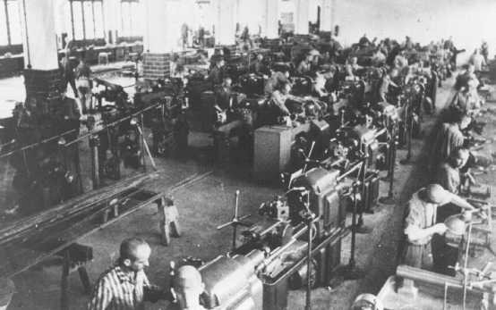 <p>Prisoners at forced labor under SS guard in an armaments factory. Dachau concentration camp, Germany, 1943.</p>