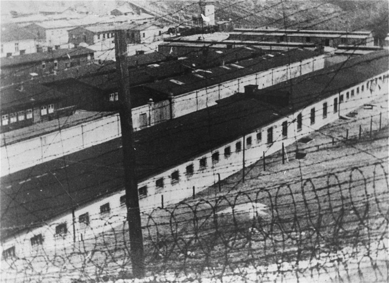 "<p>View through the barbed wire of the prisoner barracks in the <a href=""/narrative/6783"">Flossenbürg</a> concentration camp. Flossenbürg, Germany, 1942.</p>"