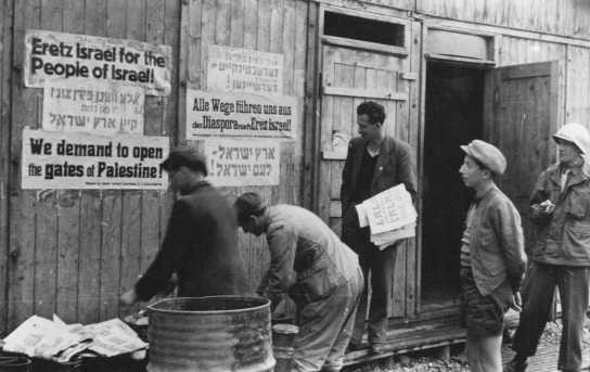 <p>Jewish displaced persons put up signs demanding open immigration into Palestine. Feldafing displaced persons camp, Germany, after May 1945.</p>