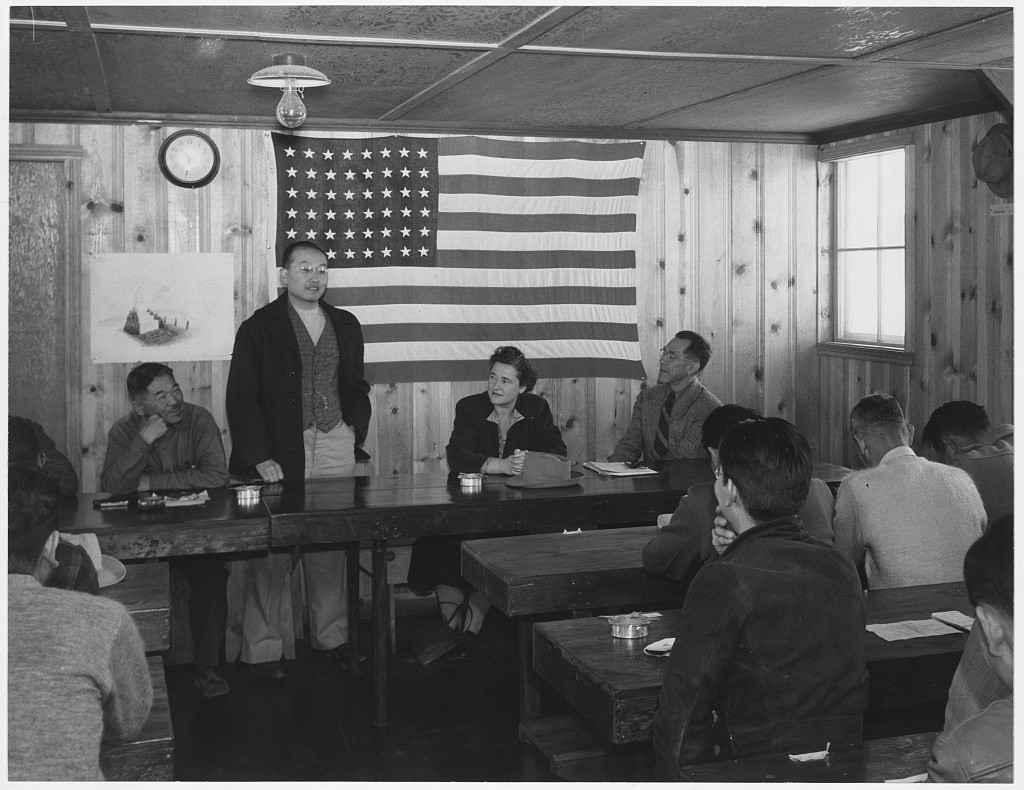 "<p>Japanese Americans hold a town hall meeting at the <a href=""/narrative/32232"">Manzanar Relocation Center</a> in California, 1943.</p>"