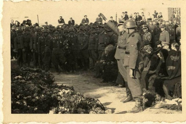 "<p>SS officer Karl Höcker salutes in front of an array of wreaths during a military funeral near Auschwitz. The original caption for the photograph reads ""Beisetzung von SS Kameraden nach einem Terrorangriff."" (Burying our SS comrades from a terror attack.) Pictured in the background are Josef Kramer and Karl Moeckel.<br /><br />This image shows the aftermath of the September 13, 1944, bombing of IG Farben in which 15 SS men died in the SS residential blocks and 28 were seriously wounded. </p>