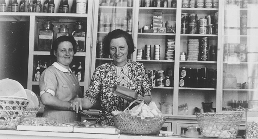 <p>Two German Jewish refugee women stand behind the counter of the Elite Provision Store (delicatessen) in Shanghai. Pictured on the left is the owner, Gerda Harpuder; on the right is her cousin Kate Benjamin. In 1939 Hans and Gerda Harpuder sold their crystal, silver, and other family possessions shipped from Berlin in order to open a grocery store in Hongkew at 737 East Broadway.</p>