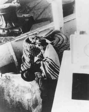 <p>Un passager juif prie à bord d'un bateau de réfugiés d'Allemagne en route pour l'Argentine en 1938.</p>