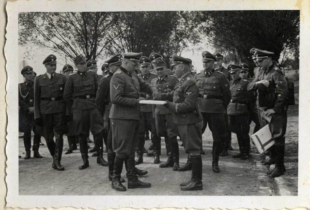 <p>September 1, 1944, Richard Baer ceremonially accepts a copy of the construction plans from the Chief of the Central Construction Directorate of the Waffen SS, SS-Sturmbannführer Karl Bischoff, celebrating the opening of an SS military hospital (SS-Lazarette). Baer was the last commandant of the Auschwitz camp. </p>