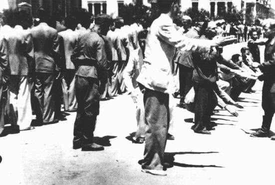 Public humiliation of Jews in Liberty Square during compulsory registration for forced labor.