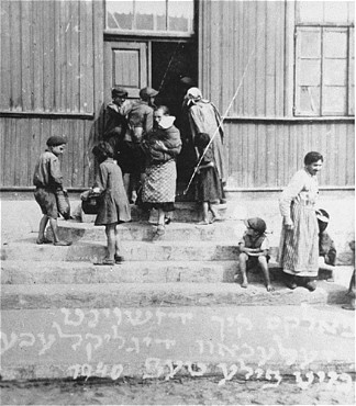 "<p>Women and children gather at the door of a soup kitchen maintained by the <a href=""/narrative/5002"">American Jewish Joint Distribution Committee</a>. The text in Yiddish reads ""The fortunate ones with full bowls."" Zelechow, Poland, 1940.</p>"