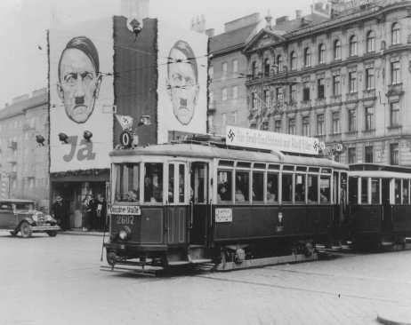 A streetcar decorated with swastikas passes billboards displaying Hitler's face. [LCID: 70073]