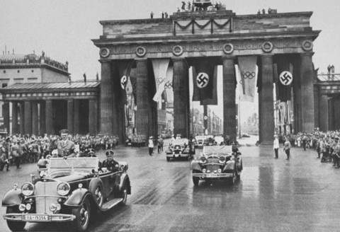 "<p>Adolf Hitler passes through the Brandenburg Gate on the way to the opening ceremonies of the <a href=""/narrative/7139"">Olympic Games</a>. Berlin, Germany, August 1, 1936.</p>"