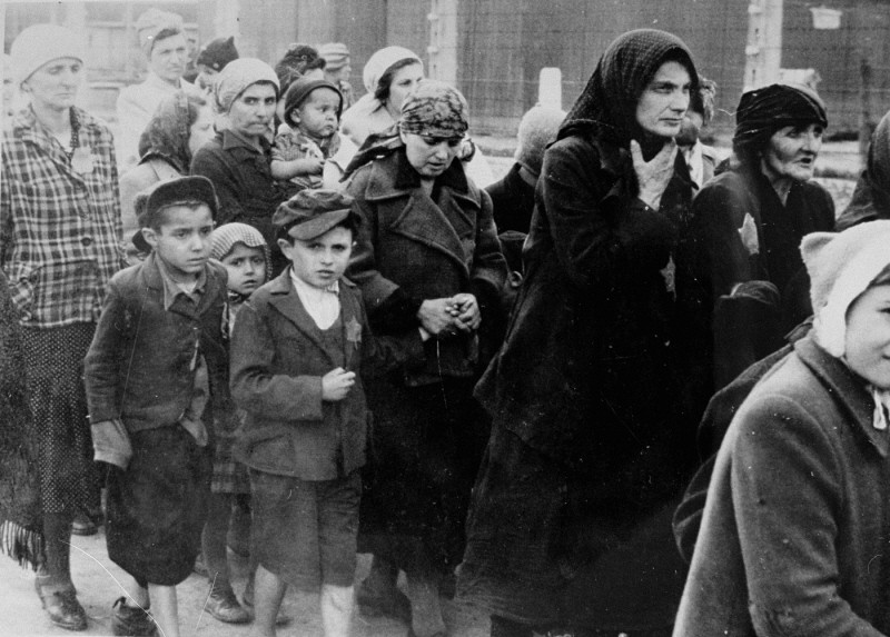 <p>Jewish women and children from Subcarpathian Rus who have been selected for death at Auschwitz-Birkenau, walk toward the gas chambers. May 1944.</p>
