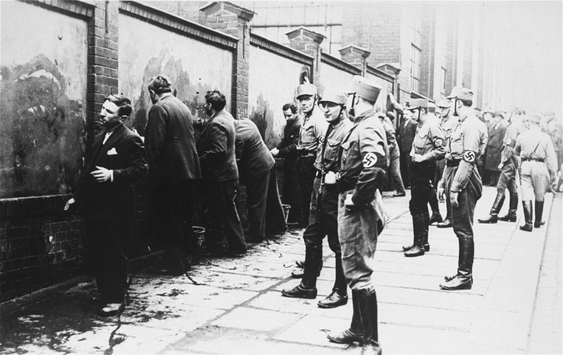 Political opponents of the Nazis, guarded by SA (Storm Troopers), are forced to scrub anti-Hitler slogans off a wall shortly after ... [LCID: 31368]