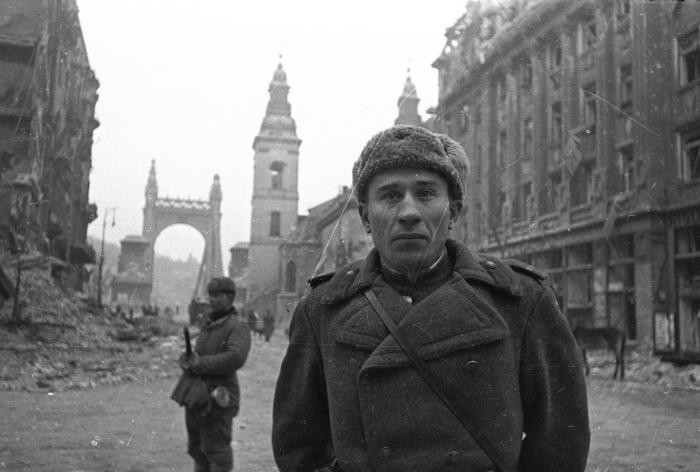 Portrait of a Soviet soldier standing on a heavily damaged street in Budapest