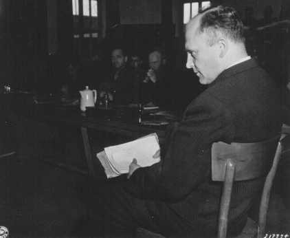 Friedrich Hoffman, holding a stack of death records, testifies about the murder of 324 Catholic priests who were exposed to malaria ... [LCID: 81911]