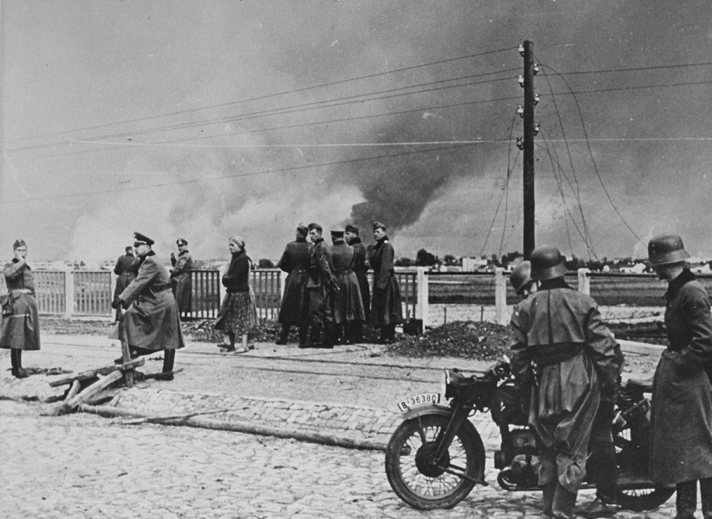"<p>German forces and Polish civilians on the outskirts of <a href=""/narrative/2014"">Warsaw</a>. In the background of the photograph, the city burns as a result of the <a href=""/narrative/2103"">German military assault</a>. Warsaw, Poland, September 1939.</p>"