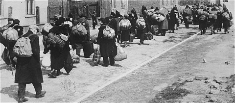 "<p>Jews carrying their possessions during deportation to the <a href=""/narrative/3852"">Chelmno</a> killing center. Most of the people seen here had previously been deported to Lodz from central Europe. Lodz, Poland, January–April 1942.</p>"