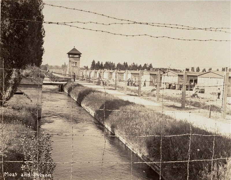 View of a section of the newly liberated Dachau concentration camp as seen through the barbed-wire fence. [LCID: 00337]