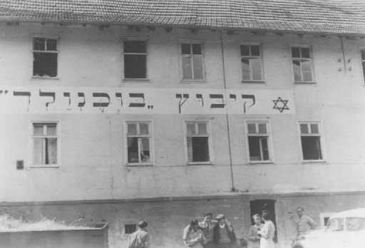 "Jewish refugees in front of the ""Kibbutz Buchenwald"" building, where Jews received agricultural training in preparation for life ... [LCID: 30118]"
