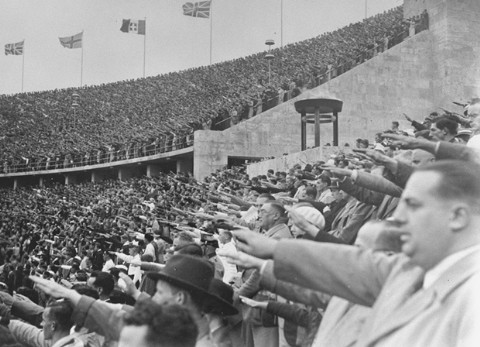 <p>In the Olympic Stadium, German spectators salute Adolf Hitler during the Games of the 11th Olympiad. Berlin, Germany, August 1936.</p>
