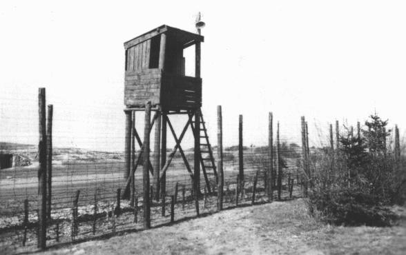 A view of one of the watchtowers and part of the perimeter fence at Orhdruf, part of the Buchenwald camp system, seen here after ... [LCID: 76502]