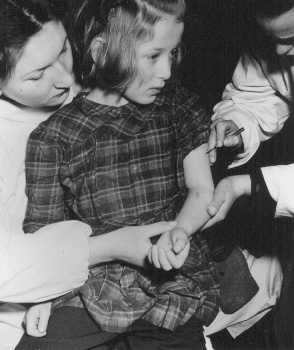 "<p>United Nations personnel vaccinate an 11-year-old concentration camp survivor who was a victim of <a href=""/narrative/3000/en"">medical experiments</a> at the Auschwitz camp. Photograph taken in the <a href=""/narrative/9359/en"">Bergen-Belsen displaced persons camp</a>, Germany, May 1946.</p>"