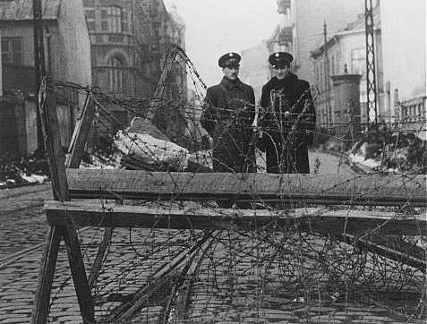 Jewish police at a barricaded entrance to the Warsaw ghetto. [LCID: 5313]