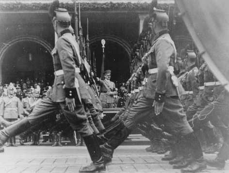 "<p>Parade of <a href=""/narrative/6434"">German police</a> before Adolf Hitler in front of Hotel Deutsches Haus, at a Nazi Party Congress rally. Nuremberg, Germany, September 10, 1937.</p>"
