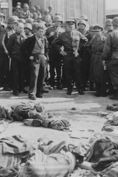 """<p>General Dwight D. Eisenhower (center, right) views the corpses of victims of the <a href=""""/narrative/7757/en"""">Ohrdruf</a> camp. Germany, April 12, 1945.</p>"""