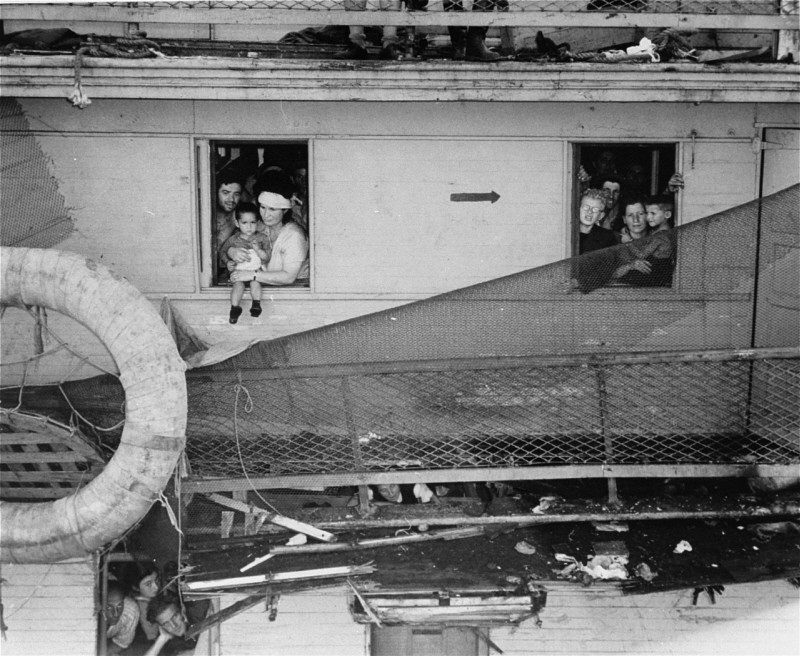 """Passengers on board the """"Exodus 1947"""" refugee ship, which has just arrived at the Haifa, Palestine port, peer out of cabin windows. [LCID: 69111]"""