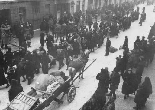 <p>یهودیان تبعید شده از آلمان و اتریش پیاده به سمت گتوی لودز می روند. لودز، لهستان، اکتبر 1941.</p>