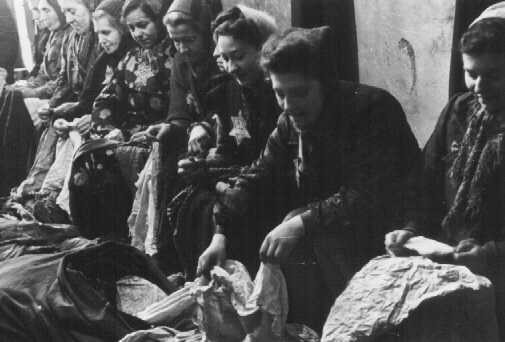 Jewish women who were seized for forced labor sort expropriated cloth. [LCID: 80417]