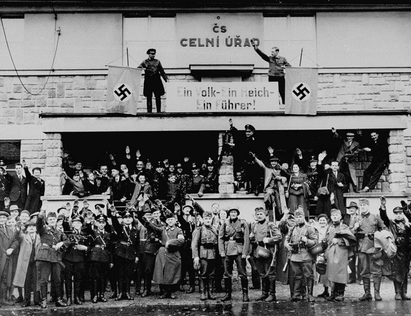 "<p>German troops marching into the Sudetenland stop at a former Czech frontier post. Nazi officials and Sudeten Germans salute the troops. The sign between the swastikas reads: ""One People, One Reich, One Führer."" Grottau, <a href=""/narrative/7295"">Czechoslovakia</a>, October 2 or 3, 1938.</p>"