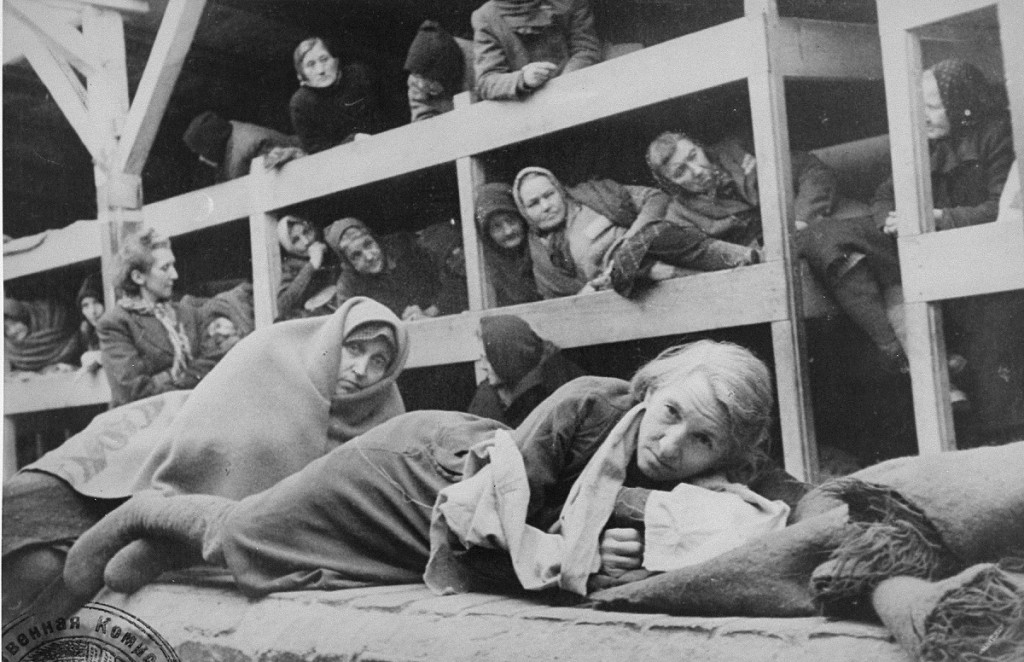 "<p>Women survivors huddled in a prisoner barracks shortly after Soviet forces liberated the <a href=""/narrative/3673"">Auschwitz</a> camp. Auschwitz, Poland, 1945.</p>"