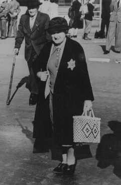 <p>یک زن سالخورده یهودی اهل آلمان که آرم مشخص کننده یهودیان را بر لباس دارد. استفاده از این آرم اجباری بود. برلین، آلمان، 27 سپتامبر 1941.</p>