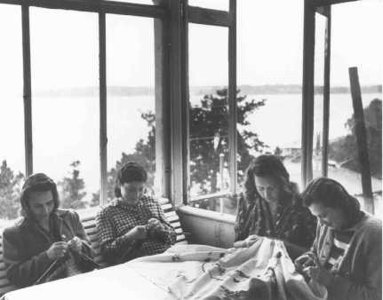 """<p>Displaced persons knitting and embroidering at a camp administered by the United Nations Relief and Rehabilitation Administration (<a href=""""/narrative/7232/en"""">UNRRA</a>). Sweden, after May 1945.</p>"""