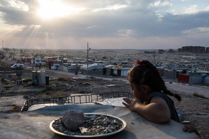 A Syrian girl looks over the Domiz refugee camp outside Duhok, Iraqi Kurdistan. [LCID: ref07]