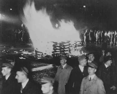 """<p>Livros """"não-alemães"""" são queimados na <em>Opernplatz</em> (Praça da Ópera). Estudantes alemães, alguns usando uniformes da SA, marcham em à luz de tochas. Berlim, 10 de maio de 1933.</p>"""